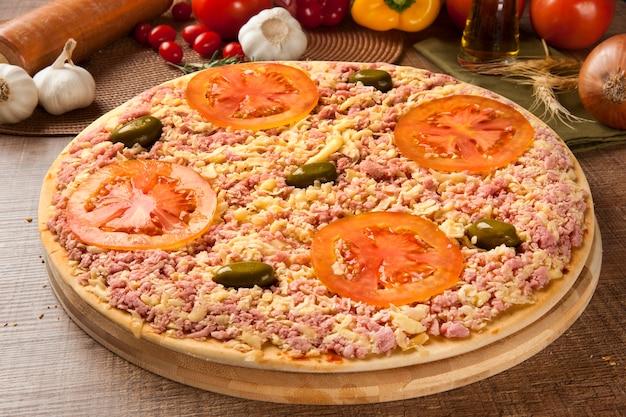 Pizza crua com queijo e presunto na mesa de madeira