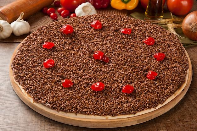 Pizza crua doce com chocolate e cereja em espaço de madeira