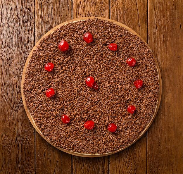Pizza crua doce com chocolate e cereja no fundo de madeira