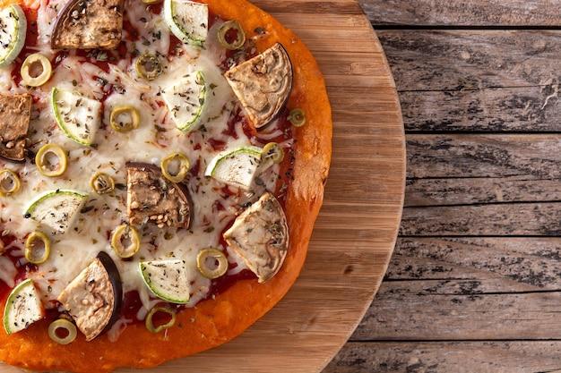 Pizza de abóbora com legumes na mesa de madeira