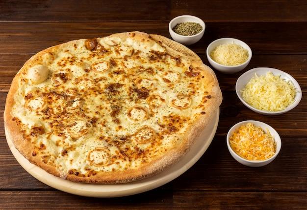 Pizza de ângulo alto com mistura de queijo e ervas secas