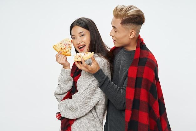 Pizza de anos quadriculados de homem e mulher nas mãos de um lanche