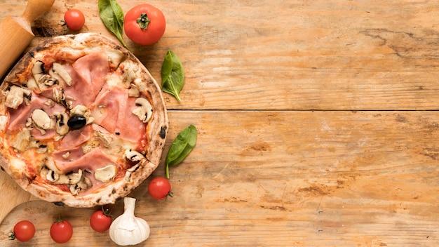 Pizza de bacon e cogumelos com legumes frescos ao longo da mesa de madeira texturizada