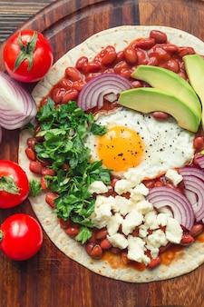 Pizza de café da manhã huevos rancheros com tomate, cebola e salsa na superfície de madeira rústica. vista do topo.
