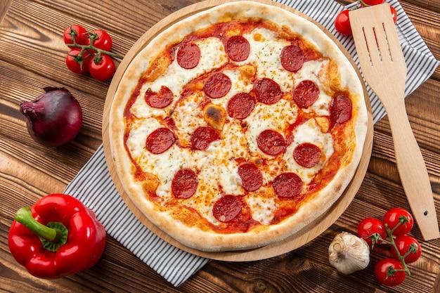 Pizza de calabresa caseira deliciosa deliciosa na mesa de madeira.