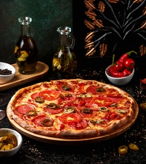 Pizza de calabresa com azeitonas na placa de madeira
