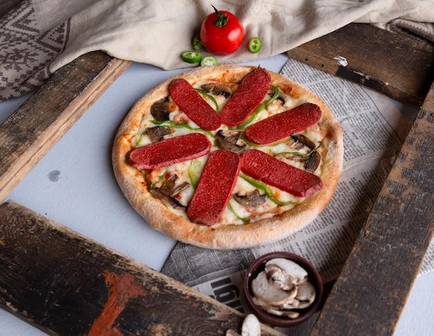 Pizza de calabresa com cogumelos e pimenta verde.