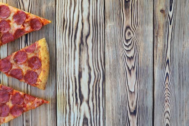 Pizza de calabresa com espinafre em um fundo de madeira