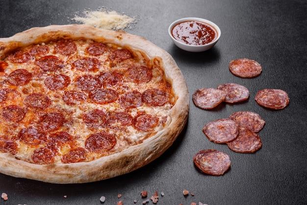 Pizza de calabresa com molho de pizza, queijo mussarela e calabresa. pizza na mesa com ingredientes