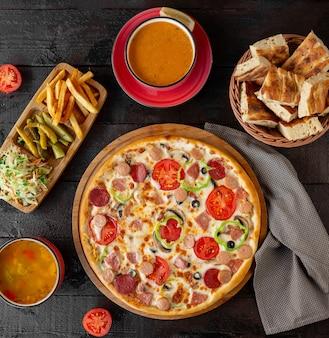 Pizza de calabresa com sopas de lentilha e legumes
