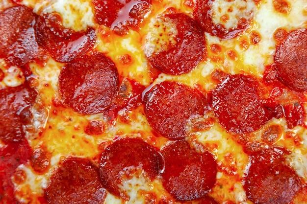 Pizza de calabresa com tomate cereja, queijo em fundo preto