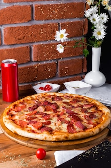 Pizza de calabresa com tomate e lata de refrigerante em cima da mesa