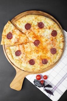 Pizza de calabresa e tomate em cima da mesa