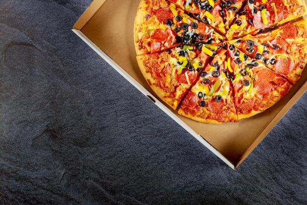 Pizza de calabresa em caixa de papelão na mesa escura