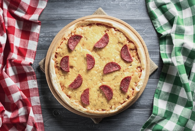 Pizza de calabresa em mesa de madeira