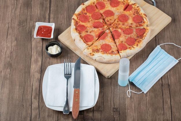 Pizza de calabresa em uma placa de madeira com molhos, prato, desinfetante para as mãos e máscara ao redor
