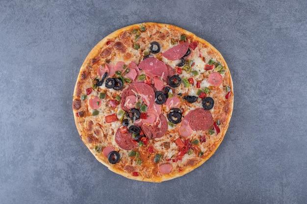 Pizza de calabresa recém-assada em fundo cinza.