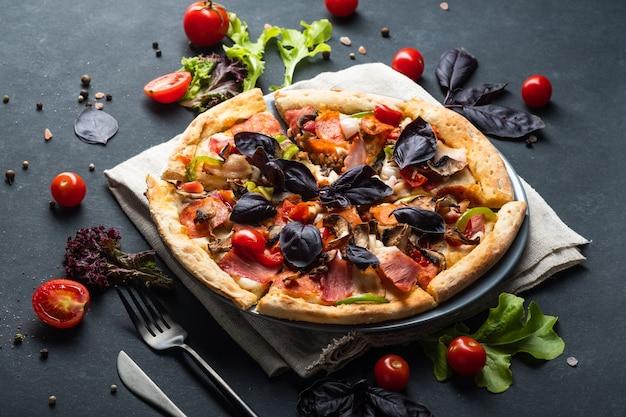 Pizza de carne caseira saborosa com tomate pepperoni bacon e manjericão em um fundo escuro