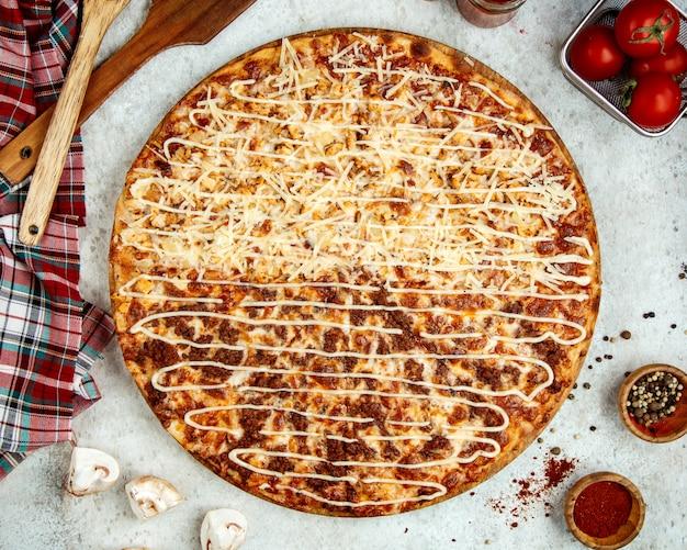 Pizza de carne com metade coberta de queijo ralado extra