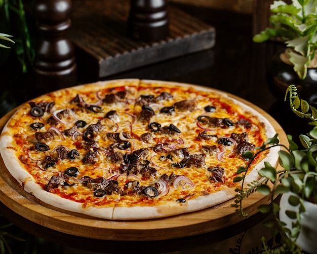 Pizza de carne com rodelas de cebola roxa, azeitona e queijo