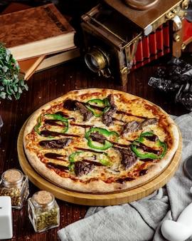 Pizza de carne de vista lateral com pimentão e molho de churrasco em uma bandeja