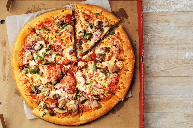Pizza de carne e pimenta repousa sobre papelão