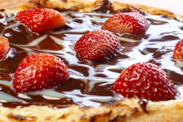 Pizza de chocolate com molho de morango e creme de leite servida em uma mesa de madeira close-up
