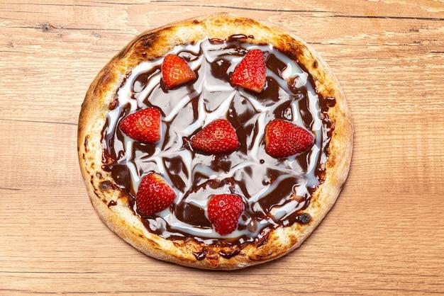 Pizza de chocolate com molho de morango e creme de leite, servida em uma vista superior de mesa de madeira.