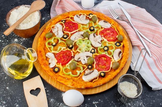 Pizza de cogumelos apimentados com tomates vermelhos, pimentão e azeitonas, tudo fatiado por dentro com azeite no fundo escuro.
