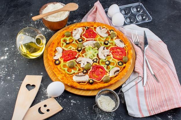 Pizza de cogumelos apimentados com tomates vermelhos, pimentões azeitonas, tudo fatiado dentro com óleo e farinha na mesa cinza.