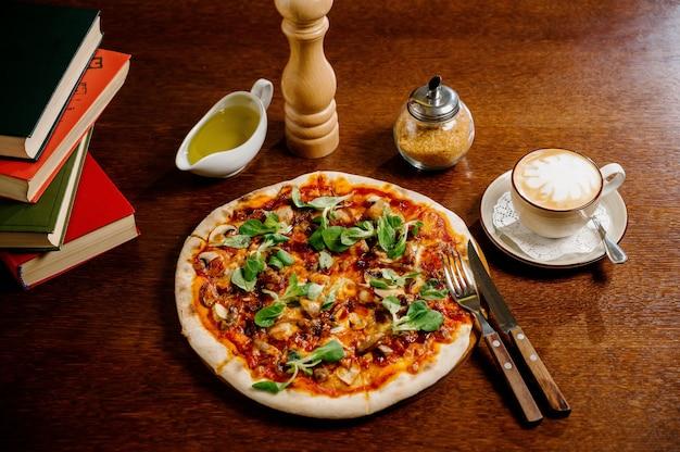 Pizza de cogumelos com adição de queijo mussarela e ervas em uma mesa de madeira, vista de cima