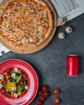 Pizza de cogumelos com salada de legumes.