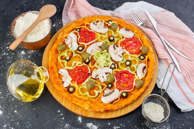 Pizza de cogumelos com tomate vermelho, pimentão, azeitonas e cogumelos, tudo fatiado dentro com óleo na mesa escura.
