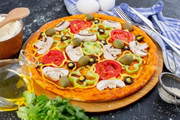 Pizza de cogumelos com tomate vermelho, pimentão, azeitonas e cogumelos, tudo fatiado dentro com ovos no escuro