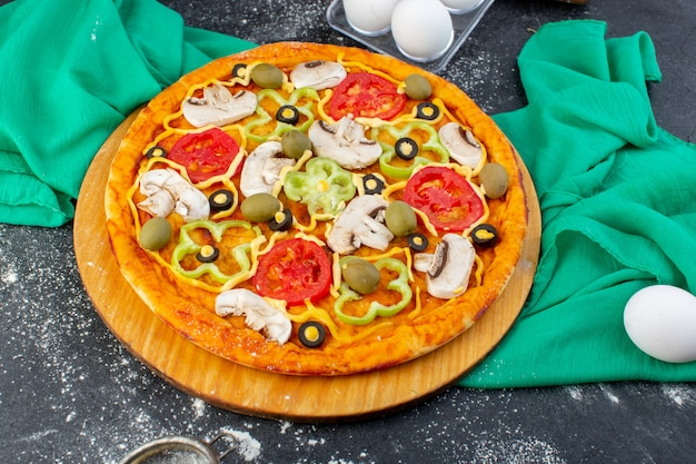 Pizza de cogumelos com tomates azeitonas cogumelos todos fatiados dentro com farinha na mesa cinza massa de tecido verde pizza comida italiana