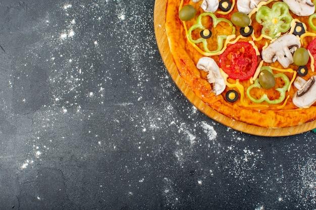 Pizza de cogumelos com tomates, azeitonas, cogumelos, tudo fatiado por dentro com azeite na mesa cinza pizza massa comida italiana