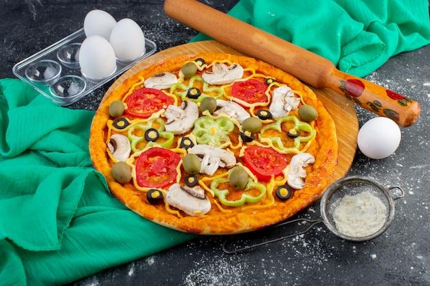 Pizza de cogumelos com tomates, azeitonas, de cima, cogumelos fatiados dentro com ovos na mesa cinza massa de tecido verde pizza comida italiana