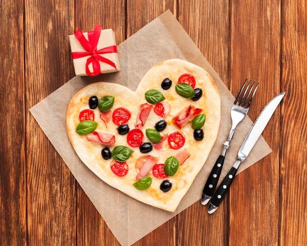 Pizza de configuração plana em forma de coração com utensílios de mesa