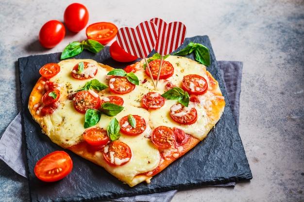 Pizza de coração com mussarela e tomate na ardósia