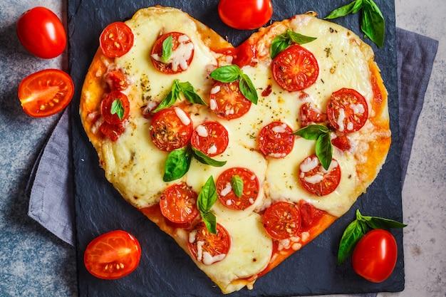 Pizza de coração com mussarela e tomate na lousa