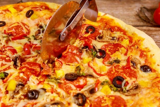 Pizza de corte com cortador em fundo de madeira. fechar-se.