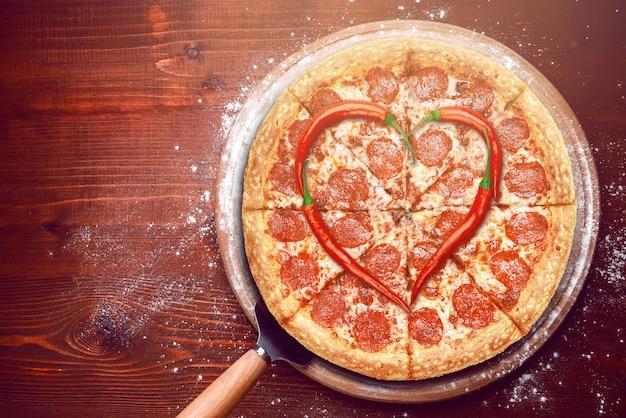 Pizza de dia dos namorados com pimentos em cima de uma pizza