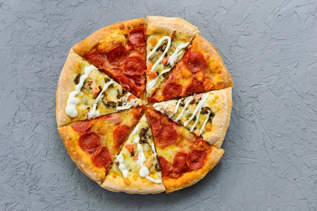 Pizza de diferentes peças em uma mesa cinza. orientação horizontal, vista superior, configuração plana.
