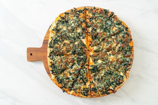 Pizza de espinafre e queijo em bandeja de madeira - estilo de comida vegana e vegetariana