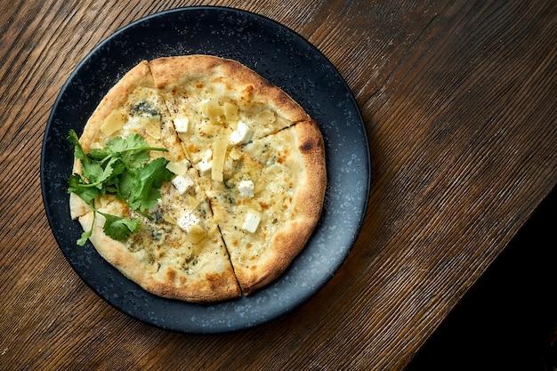 Pizza de forno a lenha com 4 tipos de queijo e molho branco sobre fundo de madeira. pizzette uma espécie de pizza italiana