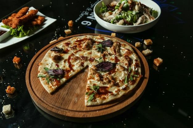 Pizza de frango vista lateral em uma bandeja com salada na mesa