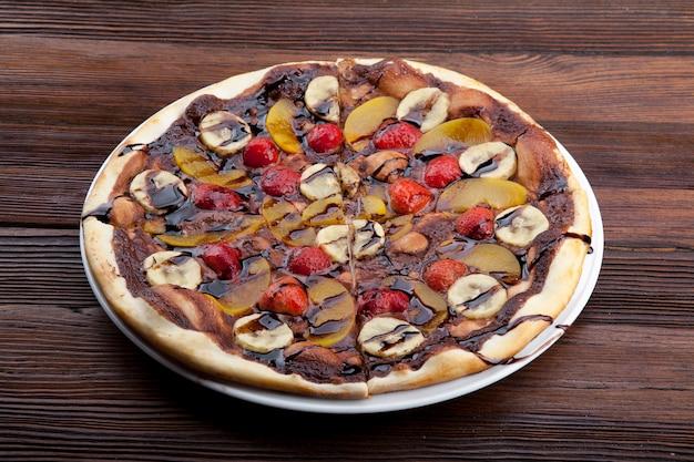 Pizza de frutas com bagas de banana e calda de chocolate