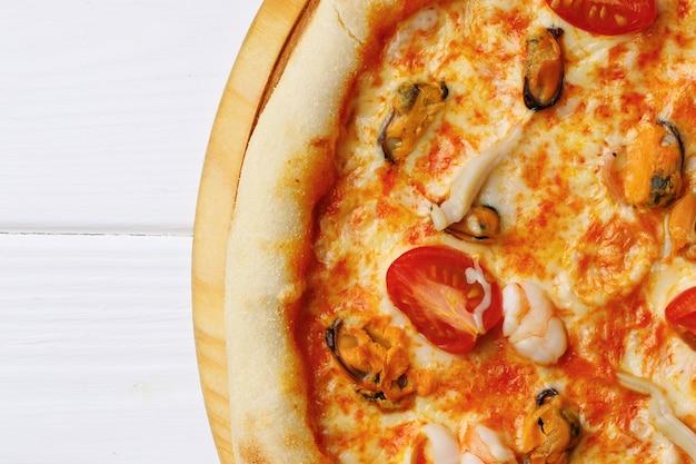 Pizza de frutos do mar a bordo em mesa de madeira branca