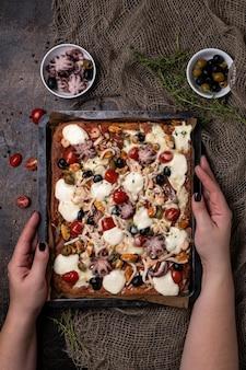 Pizza de frutos do mar caseira retangular com polvo, camarão, mexilhões e lulas em um fundo escuro de madeira. close-up e vista superior.