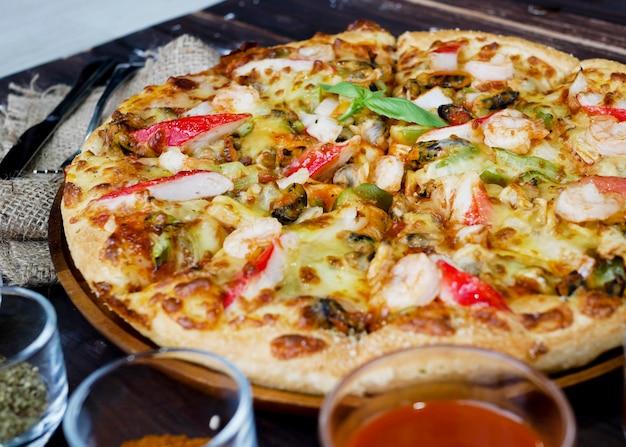 Pizza de frutos do mar e ingredientes e legumes para decorar, como alho e cogumelos com alho e pimenta
